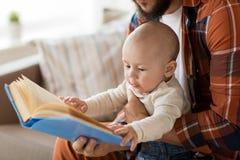 Den lyckliga fadern och behandla som ett barn lite pojken med den hemmastadda boken Arkivbild