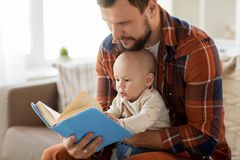 Den lyckliga fadern och behandla som ett barn lite pojken med den hemmastadda boken Royaltyfri Fotografi