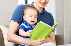 Den lyckliga fadern och behandla som ett barn lite sonen med boken hemma royaltyfri fotografi