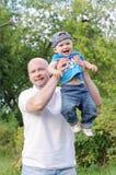 Den lyckliga fadern och behandla som ett barn sonen som utomhus går Royaltyfri Fotografi