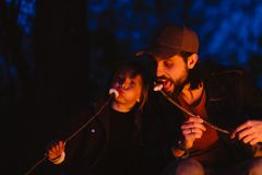 Den lyckliga fadern och hans lilla sonen som sitter på, loggar in skogen framme av en brand och ätamarshmallower från royaltyfri foto