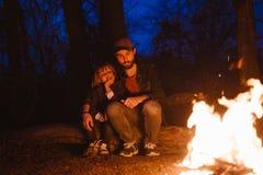 Den lyckliga fadern och hans lilla sonen som tillsammans sitter på, loggar in framdelen av en brand i en vandring i skogen på nat arkivbild