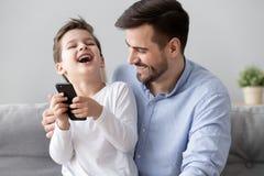 Den lyckliga fadern och den lilla sonen har gyckel hemma tillsammans royaltyfria foton
