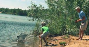 Den lyckliga fadern och sonen fiskar, sonhjälpen som hans fader drar ut den fångade fisken, bär fiskstopparen Lyckligt arkivfilmer