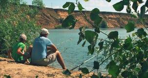Den lyckliga fadern och sonen sitter på flodbanken, fiske, farsa, och sonen fiskar i morgonen lycklig familj stock video