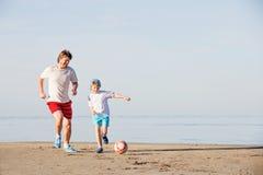 Den lyckliga fadern och sonen spelar på fotboll eller fotboll Arkivfoto