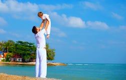Den lyckliga fadern och sonen tycker om liv på den tropiska ön Fotografering för Bildbyråer