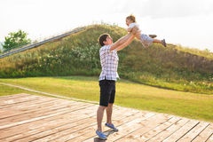 Den lyckliga fadern som rymmer den lilla ungen i armar som kastar behandla som ett barn i luft begrepp av den lyckliga familjen,  Arkivfoton