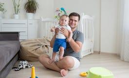 Den lyckliga fadern som spelar med hans 9 gamla malar, behandla som ett barn pojken på golv på l Fotografering för Bildbyråer