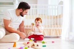 Den lyckliga fadern som spelar med spädbarnet, behandla som ett barn pojken på soligt barnkammarerum Royaltyfri Foto