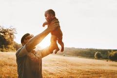 Den lyckliga fadern som upp rymmer sp?dbarnet, behandla som ett barn utomhus- ferie f?r faderdag royaltyfria bilder
