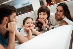 Den lyckliga familjen är avslappnande på madrassen i ortopediskt möblemanglager Den stora familjen kontrollerar tillsammans softn arkivbilder