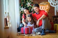 Den lyckliga familjen öppnar gåvor Royaltyfri Fotografi