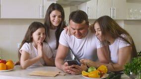 Den lyckliga familjen använder en Smartphone Royaltyfri Foto