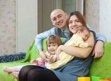 Den lyckliga familjen av fyra med nyfött behandla som ett barn Royaltyfri Foto