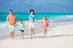 Den lyckliga familjen av fyra på en tropisk strand tycker om sommarsemester Arkivfoto