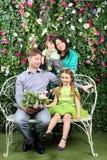 Den lyckliga familjen av fyra sitter på den vita bänken med gruppen av blommor Arkivbild