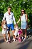 Den lyckliga familjen av fyra som har, vilar utomhus- i Arkivfoton