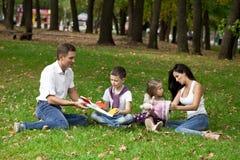 Den lyckliga familjen av fyra som vilar i hösten, parkerar Arkivfoto