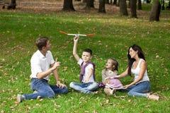 Den lyckliga familjen av fyra som vilar i hösten, parkerar Royaltyfri Bild