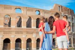 Den lyckliga familjen av fyra tycker om italiensk semester på Colosseum bakgrund Italiensk europeisk familjsemester i Rome Fotografering för Bildbyråer