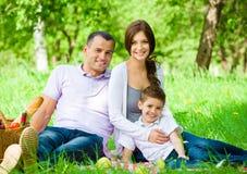 Den lyckliga familjen av tre har picknicken i gräsplan att parkera Arkivfoto