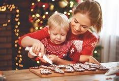 Den lyckliga familjen bakar julkakor royaltyfri fotografi