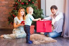Den lyckliga familjen, behandla som ett barn den hållande julgåvan för pojken Fotografering för Bildbyråer