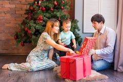 Den lyckliga familjen, behandla som ett barn den hållande julgåvan för pojken Royaltyfri Foto