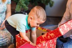 Den lyckliga familjen, behandla som ett barn pojken öppnar julgåvan Arkivbild