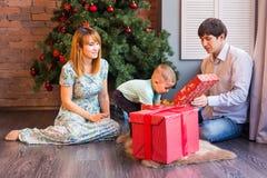 Den lyckliga familjen, behandla som ett barn pojken öppnar julgåvan Fotografering för Bildbyråer