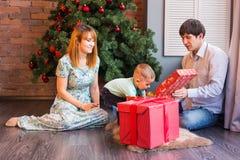Den lyckliga familjen, behandla som ett barn pojken öppnar julgåvan Arkivfoton