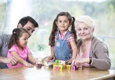 Den lyckliga familjen för tre utveckling som spelar med alfabet, blockerar hemma Fotografering för Bildbyråer