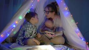 Den lyckliga familjen, fostrar berättar känslomässigt en saga till hennes söner som sitter i vigvammet i afton stock video