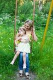 Den lyckliga familjen fostrar utomhus och ungen, barnet, dottern som ler p Arkivfoto