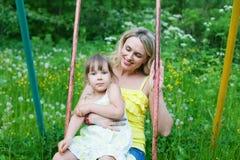 Den lyckliga familjen fostrar utomhus och ungen, barnet, dottern som ler p Fotografering för Bildbyråer