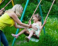 Den lyckliga familjen fostrar utomhus och ungen, barnet, dottern som ler p Arkivfoton