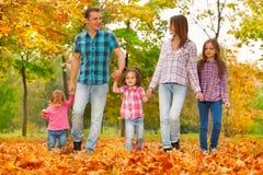Den lyckliga familjen går i Autumn October parkerar Royaltyfria Bilder