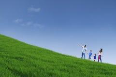 Den lyckliga familjen går på grönt fält och rymmer händer Arkivbild