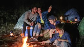 Den lyckliga familjen gör fotoet på mobiltelefonen nära lägereld i skogen, föräldrar med childs in i loppläger gör selfifotoet, stock video
