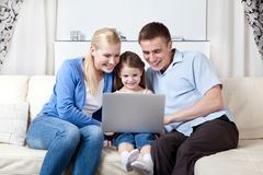 Den lyckliga familjen gör köp till och med internet Royaltyfri Foto