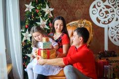 Den lyckliga familjen ger gåvor arkivfoto