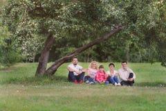 Den lyckliga familjen har en vila under trädäpplet Arkivbild