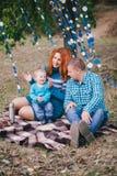 Den lyckliga familjen har födelsedagpartiet med blåa garneringar i skog Arkivbild