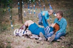 Den lyckliga familjen har födelsedagpartiet med blåa garneringar i skog Arkivfoton