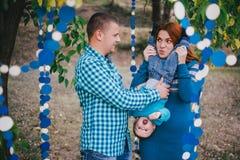 Den lyckliga familjen har födelsedagpartiet med blåa garneringar i skog Arkivfoto