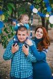Den lyckliga familjen har födelsedagpartiet med blåa garneringar i skog Arkivbilder