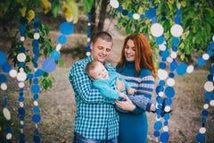 Den lyckliga familjen har födelsedagpartiet med blåa garneringar i skog Royaltyfri Foto