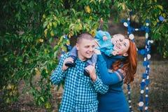 Den lyckliga familjen har födelsedagpartiet med blåa garneringar i skog Royaltyfri Fotografi