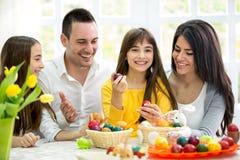 Den lyckliga familjen har gyckel med påskägg Fotografering för Bildbyråer